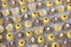 Petits gâteaux de Pâques avec des oeufs, des nids, et des poussins Photos stock