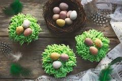 Petits gâteaux de Pâques décorés du givrage et de la Pâques c d'herbe verte Photographie stock