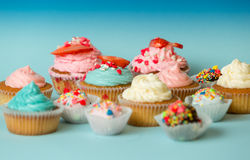 Petits gâteaux et sucreries colorés faits maison sur le fond bleu Images stock