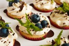 Petits gâteaux faits main avec de la crème de beurre, le chocolat râpé, les feuilles en bon état et les myrtilles dans un boîtier Images stock