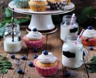 Petits gâteaux faits maison de myrtille avec un pot de lait sur un fond en bois, style rustique Photo stock