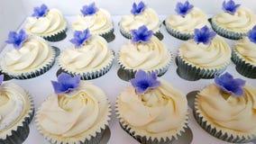 Petits gâteaux givrés par ivoire avec les pétunias pourpres Image stock