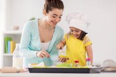 Petits gâteaux heureux de cuisson de mère et de fille à la maison Photographie stock libre de droits