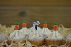 Petits gâteaux heureux de Pâques avec le buttercream et décorés des carottes et du fond glacés de paille Images stock