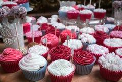 Petits gâteaux lumineux avec le givrage rose et blanc à un banquet Image libre de droits
