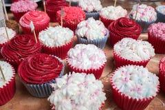 Petits gâteaux lumineux avec le givrage rose et blanc à un banquet Photographie stock libre de droits