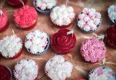 Petits gâteaux lumineux avec le givrage rose et blanc à un banquet photographie stock