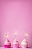 Petits gâteaux roses avec des cierges magiques Images libres de droits