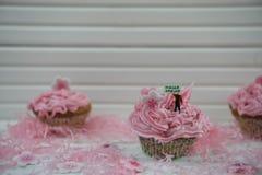 Petits gâteaux roses délicieux décorés d'une figurine miniature de personne tenant un signe avec des mots bonjour de ressort et d Photographie stock libre de droits