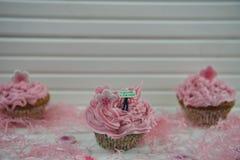 Petits gâteaux roses délicieux décorés d'une figurine miniature de personne tenant un signe avec des mots bonjour de ressort et d Photos stock