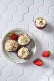 Petits gâteaux rouges de velours avec des fraises Photos stock