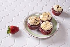 Petits gâteaux rouges de velours avec des fraises Photographie stock libre de droits