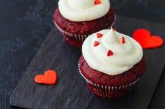Petits gâteaux rouges de velours avec le givrage de fromage fondu photo stock