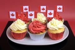 Petits gâteaux rouges et blancs avec les drapeaux nationaux canadiens de feuille d'érable - fin. Photographie stock libre de droits