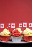 Petits gâteaux rouges et blancs avec les drapeaux nationaux canadiens de feuille d'érable - verticale avec le copyspace. Photographie stock libre de droits