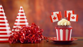 Petits gâteaux rouges et blancs de thème avec les drapeaux canadiens de feuille d'érable Image stock