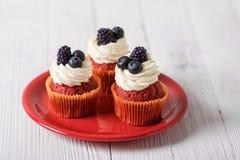Petits gâteaux rouges savoureux de velours avec la myrtille et la mûre images stock