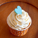 Petits gâteaux savoureux avec de la crème de beurre sur le bois Photographie stock libre de droits