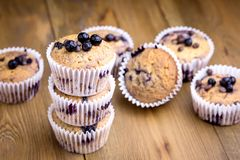 Petits gâteaux savoureux de petit pain avec des myrtilles sur une pile en bois de fond des petits pains faits maison horizontaux Photo libre de droits