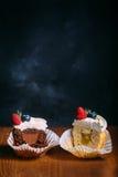 Petits gâteaux savoureux frais avec des baies Foyer sélectif Fond en bois foncé Style rustique, endroit pour le texte coupez les  Photos libres de droits