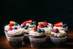 Petits gâteaux savoureux frais de chocolat avec des baies Foyer sélectif Fond en bois foncé Style rustique, endroit pour le texte Image stock