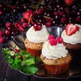 Petits gâteaux sur le plateau en métal décoré des baies Photographie stock libre de droits