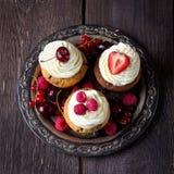 Petits gâteaux sur le plateau en métal décoré des baies Image libre de droits