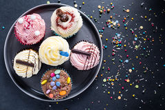 Petits gâteaux vibrants de plat sur le fond foncé Image stock