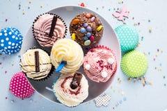 Petits gâteaux vibrants sur le fond bleu, concept de nourriture de partie Photos stock
