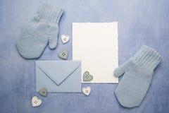 Petits gants de bébé, carte vierge et evelop sur le fond bleu de tissu Configuration plate Vue supérieure Photographie stock libre de droits