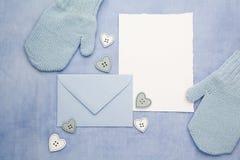 Petits gants de bébé, carte vierge et evelop sur le fond bleu de tissu Configuration plate Vue supérieure Photographie stock