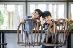 Petits garçon et fille asiatiques en café avec le visage de sourire et le Ca de regard Photographie stock