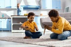 Petits garçons agréables jouant avec des dinosaures de jouet sur le plancher Images libres de droits