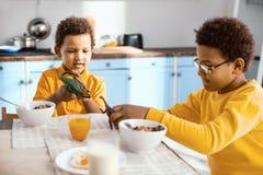 Petits garçons agréables jouant avec des jouets au petit déjeuner Photographie stock libre de droits