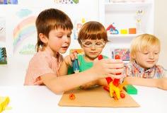 Petits garçons avec des pinces de jouet dans la salle de classe Photos stock
