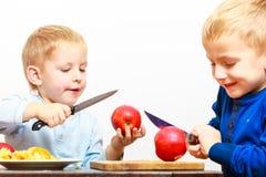Petits garçons coupant la pomme avec un couteau de cuisine photographie stock