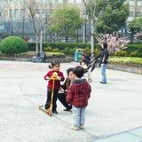 Petits garçons et filles asiatiques jouant en parc public Photo stock