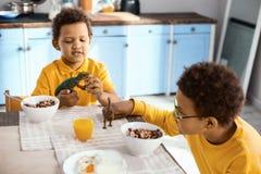 Petits garçons gais jouant tout en prenant le petit déjeuner Photos stock