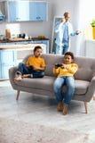 Petits garçons gais s'asseyant sur le sofa et jouant des jeux vidéo Images stock