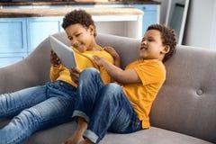 Petits garçons heureux observant la bande dessinée et rire Photographie stock