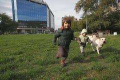 Petits garçons jouant et courant avec leurs chiens sur la pelouse Image stock