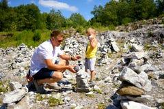 Petits garçons mignons et son père construisant ensemble la tour des pierres Image stock