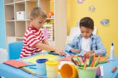 Petits garçons mignons faisant l'art dans la salle de classe Photos stock