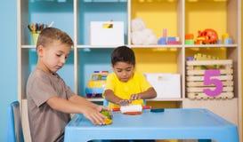 Petits garçons mignons jouant avec modeler l'argile dans la salle de classe Image stock