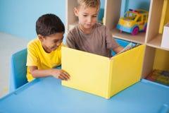 Petits garçons mignons lisant au bureau dans la salle de classe Photographie stock