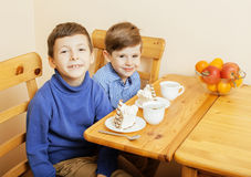 Petits garçons mignons mangeant le dessert sur la cuisine en bois Image stock