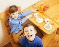 Petits garçons mignons mangeant le dessert sur la cuisine en bois Photos libres de droits