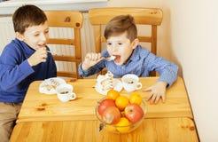 Petits garçons mignons mangeant le dessert sur la cuisine en bois Image libre de droits