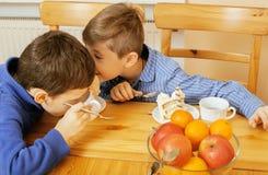 Petits garçons mignons mangeant le dessert sur la cuisine en bois Images libres de droits