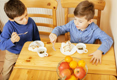 Petits garçons mignons mangeant le dessert sur la cuisine en bois Photo stock